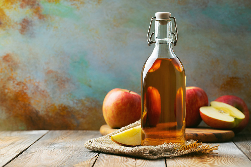 Bottle of apple cider vinegar with apples in the background
