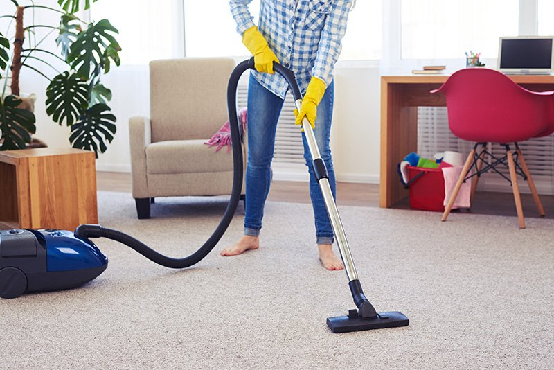 Vacuuming carpets in the house