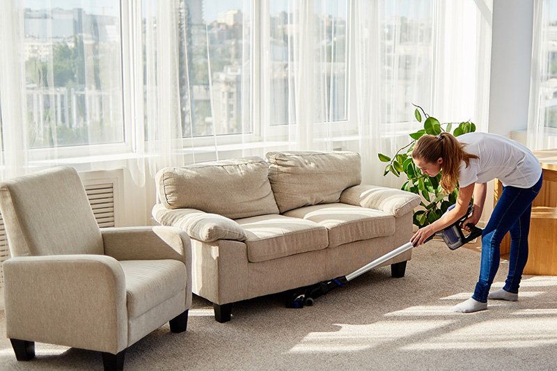 Woman in white shirt and jeans vacuuming carpet under couch