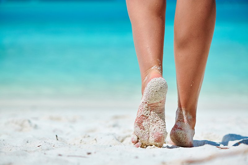 Woman with bare feet walking on sand on beach