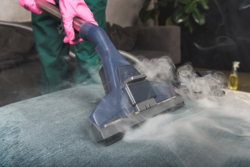 Person steam cleaning sofa with vacuum cleaner inside home